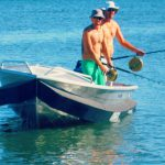 Two men fishing on same side of small boat